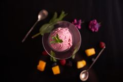 Ice cream with beets in a glass ice-cream bowl decorated with mint leaves on a dark background with slices of mango, blackberry, r stock image