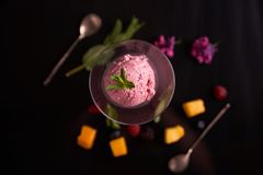 Ice cream with beets in a glass ice-cream bowl decorated with mint leaves on a dark background with slices of mango, blackberry, r stock images