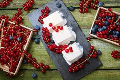Ice cream with berries. View from above. Creamy ice cream and boxes with red currants on an old wooden table Royalty Free Stock Photos