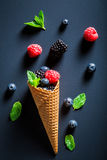 Ice cream with berry fruits in cone as a concept. On blackboard stock photography