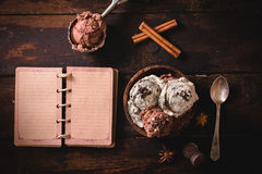 Ice cream and blank book. Ice cream in wooden bowl and blank book on wooden background Stock Photo