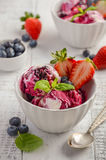 Ice cream with blueberries and strawberries in white bowl on white wooden background Royalty Free Stock Image