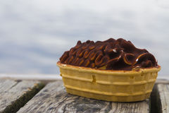 Ice Cream Boat by the Sea. An Ice Cream Boat sitting on a wooden jetty looking out towards the sea Stock Photo