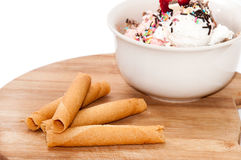 Ice cream in the bowl and sweet sticks on the table Royalty Free Stock Images