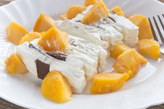 Ice cream cake with peach slices. In plate Royalty Free Stock Photo