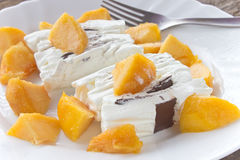 Ice cream cake with peach slices. In plate Royalty Free Stock Image