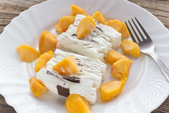 Ice cream cake with peach slices. In plate Royalty Free Stock Images