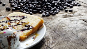 Ice cream and cake. Put on a wood table with dark roasted coffee beans Royalty Free Stock Photos