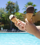 Ice cream in a child's hand close-up. On the background of the swimming pool Royalty Free Stock Photography