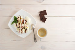 Ice cream with chocolate and coffee in a mag. Ice cream with chocolate and spoon on the plate, slices of black chocolate and coffee in a mug on white rustic Stock Images