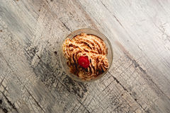 Ice cream with chocolate crumb and cherry on wood background Royalty Free Stock Photography