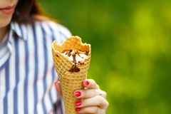 Ice cream close-up. Young beautiful girl with long flowing hair holding ice cream royalty free stock photography