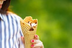 Ice cream close-up. Young beautiful girl with long flowing hair holding ice cream. Bright sunny day royalty free stock image