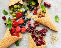 Ice cream cone with berries. On a stone background royalty free stock images