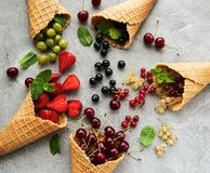 Ice cream cone with berries. On a stone background stock photo