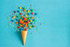 Ice cream cone with colorful lollipop and multicolored sweets royalty free stock image