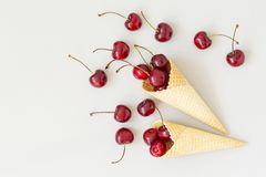 Ice cream cone filled with cherries on a grey light background. Fresh cherry in a waffle cone. Summer concept. Ice cream cone filled with cherries on a grey stock images