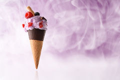 Ice cream cone flavored berries cold steam. Ice cream cone flavored berries. Elevated on reflective table and garnished with blueberries and raspberries. With Royalty Free Stock Image