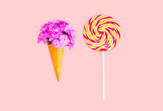 Ice cream cone flowers and colorful lollipop caramel on stick over pink background Royalty Free Stock Image