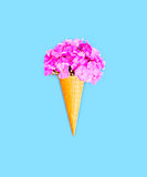 Ice cream cone with flowers over blue background Royalty Free Stock Photo