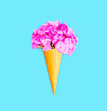 Ice cream cone with flowers over blue background Royalty Free Stock Photography