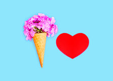 Ice cream cone with flowers and red heart shape over blue colorful background. Top view Royalty Free Stock Photo