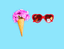 Ice cream cone with flowers and red sunglasses heart shape over blue background Royalty Free Stock Images