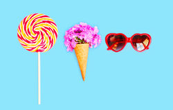 Ice cream cone with flowers sunglasses heart shape lollipop caramel on stick over blue background Stock Images