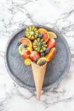 Ice cream cone with fresh fruits. Ice cream waffle cone with fresh ripe fruits stock images