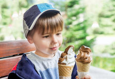 Ice cream cone  - yummy! Cute boy with two delicious ice cream. Royalty Free Stock Image