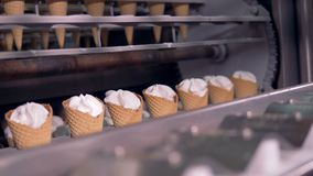 Ice-cream cones are being relocated from a rotary conveyor to a linear one. 4K stock video