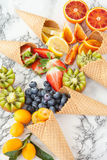 Ice cream cones with fresh fruits. Ice cream waffle cones with fresh ripe fruits royalty free stock image