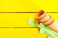 Ice cream cones and green plastic spoons Stock Photos