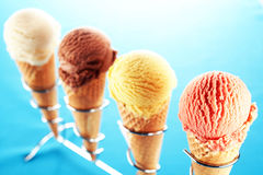 Ice cream cones on metal holder. Selective focus view on diagonal row of strawberry, lemon, chocolate and vanilla ice cream cones lined up on stainless steel Stock Photos