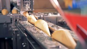 Ice-cream cones are moving along the metal duct towards wrapping belt. 4K stock footage