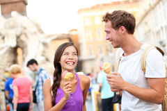 Ice cream - couple eating gelato in Rome. On Piazza Navona. Couple eating ice cream on vacation travel in Italy, Europe. Smiling happy young couple in love Stock Photo