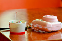 Ice cream in a cup and camera on a wooden table. Stock Photography