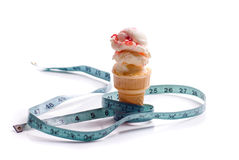 Ice Cream Diet. Concept image of a diet featuring an ice cream cone with strawberry ice cream and a measuring tape shot on white Royalty Free Stock Image