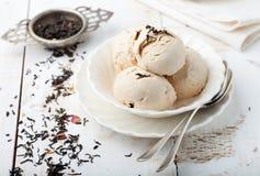 Ice cream with Earl grey tea flavor. White ceramic bowl. Ice cream with Earl grey tea flavor in white ceramic bowl on a white wooden background Stock Image
