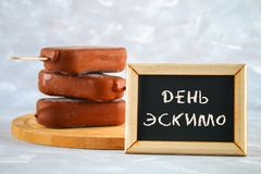 Ice cream eskimo pie on a stick with the text in Russian - Day eskimo pie. Stock Photo