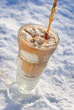 Ice Cream Float. An ice cream float sitting in the snow while someone pours in the colo Stock Photos