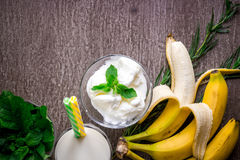 Ice cream with fresh banana and mint on wooden table. Banana smoothie. Top view. Copy space. Flat lay. Still life Royalty Free Stock Photo