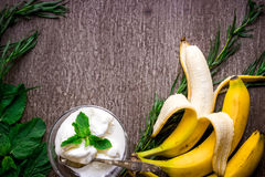Ice cream with fresh banana and mint on wooden table. Top view. Copy space. Flat lay. Still life Stock Photography
