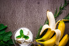 Ice cream with fresh banana and mint on wooden table. Top view. Copy space. Flat lay. Still life Royalty Free Stock Images