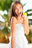 Ice cream girl excited. And happy eating ice cream cone on beach during summer vacation. Lovely sweet mixed race Asian Chinese / Caucasian young woman outside Royalty Free Stock Images