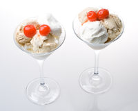 Ice-cream a glass. Ice-cream with a cherry in a glass on a white background royalty free stock images