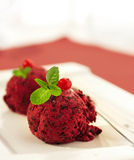 Ice-cream globule with a currant. And mint on a red napkin Royalty Free Stock Image