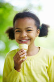 Ice-cream happiness. Portrait of happy girl eating ice-cream and looking at camera Stock Photography