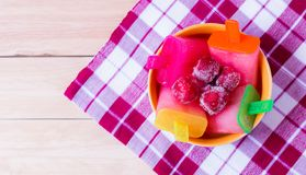 Ice cream. Homemade strawberry popsicles with frozen strawberry in a bowl on tablecloth Royalty Free Stock Images