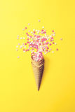 Ice Cream Horn or Cone with Sweethearts on a Yellow Background. Top View. Fashion Style. Love, Valentine`s Day or Creative Concept. Top view Royalty Free Stock Photography